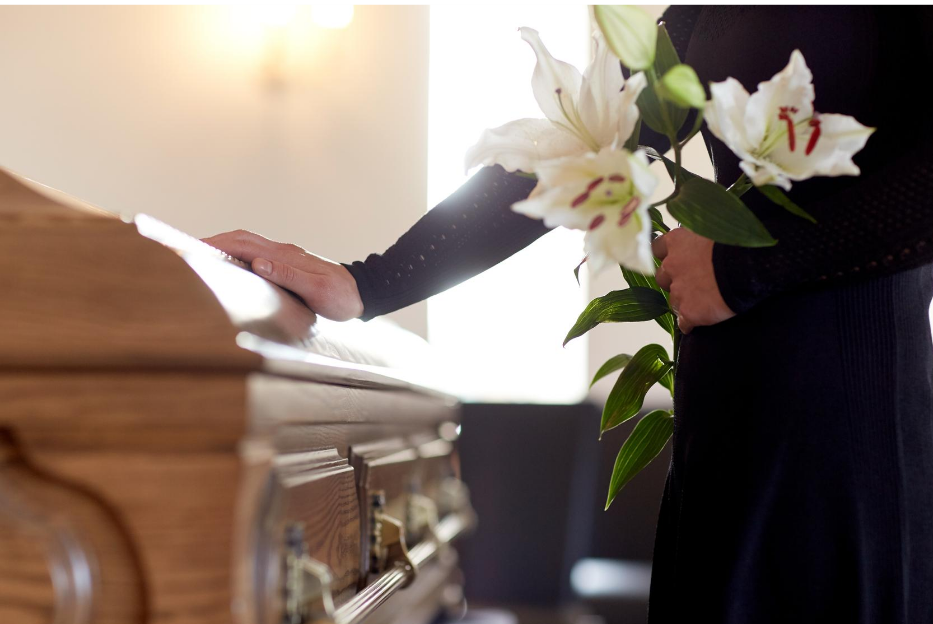 man placing hand on casket | affordable funeral | overnight caskets