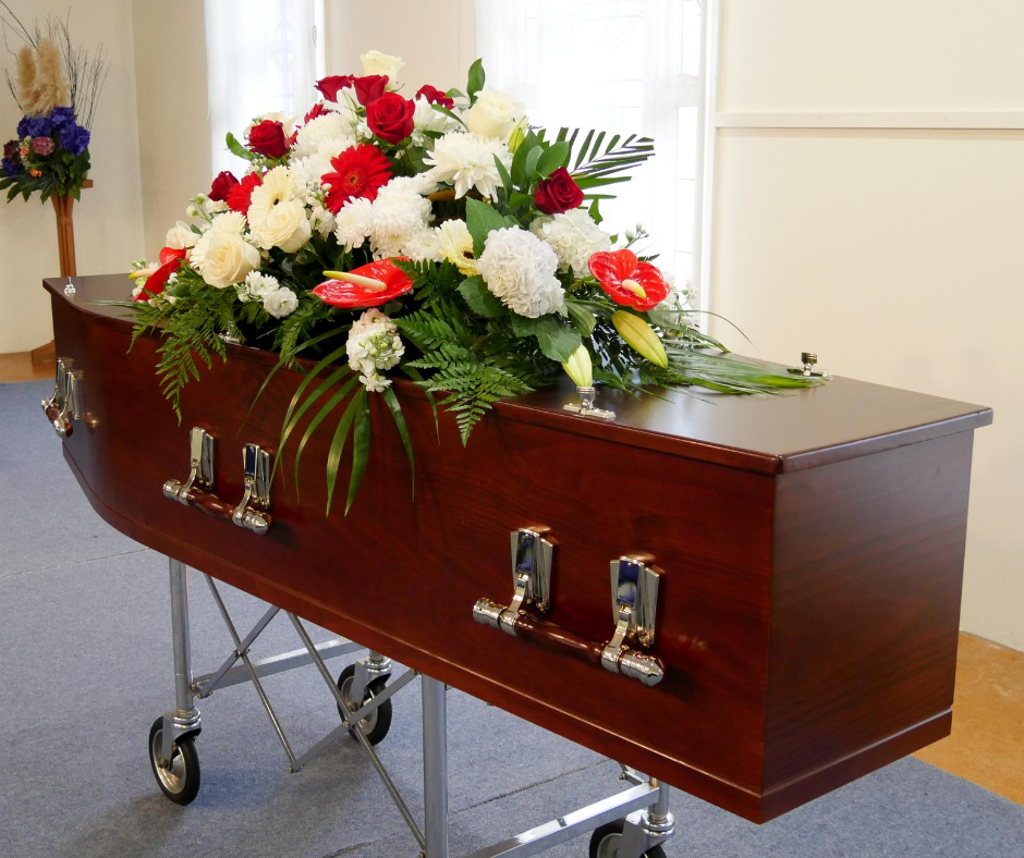 image of a wood casket with flowers on it | pre-need funeral | Overnight Caskets