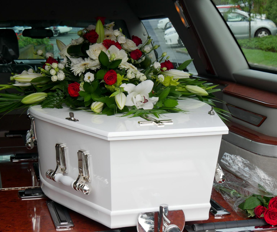 white casket with flower on it in a hearse | Pre-Purchase a Casket | Overnight Caskets
